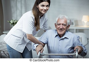 Nurse helping disabled senior man with standing