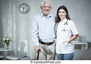 Female doctor and elder man at home