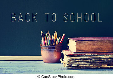 pencils, old books and the text back to school on a...