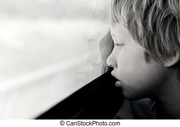 Cute 7 years old boy looking through the window in the train