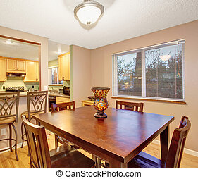 Small kitchen and dining rom with square table.