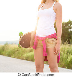 Anonymous teenage girl with skateboard, image with sunflare