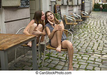 Two girls whispering sitting on the
