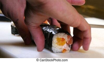 Sushi Chef Presenting Futomaki Roll