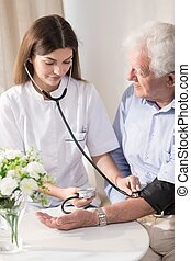 Senior man with hypertension having measured blood pressure