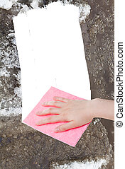 hand deletes melting snow by pink rag - weather concept -...