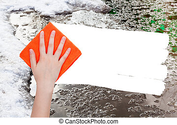 hand deletes melting snow by orange rag - weather concept -...