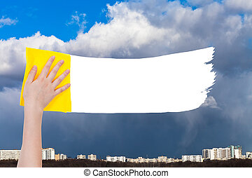 hand deletes rainy clouds over city by yellow rag - weather...
