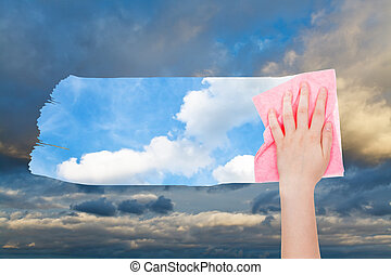 hand deletes dark cloudscape by pink cloth - weather concept...