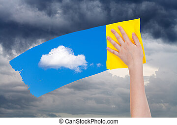 hand deletes rain clouds by yellow cloth - weather concept -...
