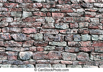 Stone wall closeup, horizontal stonewall pattern background, old aged weathered red and grey grunge limestone dolomite calcium carbonate hard sedimentary slate slab rock texture, natural grungy textured bricks, beige, yellow, reddish, gray brick vintage