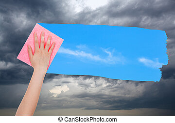 hand deletes storm clouds by pink cloth - weather concept -...