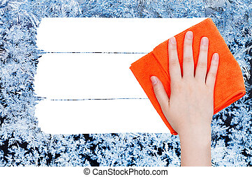 hand deletes winter frozen texture on glass by rag - weather...