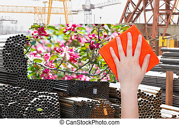 hand deletes industrial landscape by orange cloth - ecology...