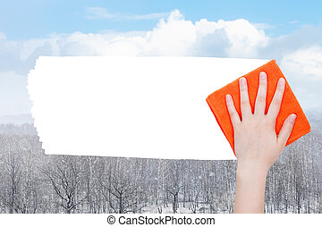 hand deletes snow over forest by orange rag - weather...