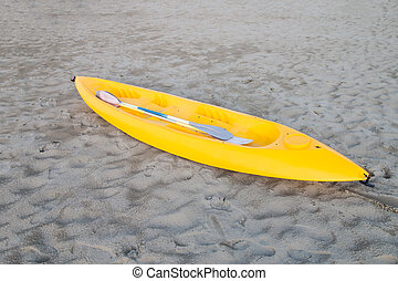 yellow canoe on a light sandy beach - yellow plastic canoe...