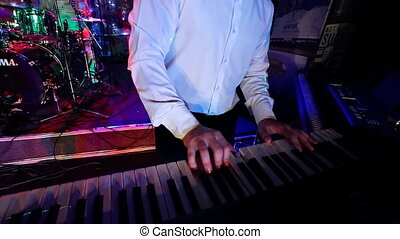 hands of musician playing keyboard in concert with shallow...