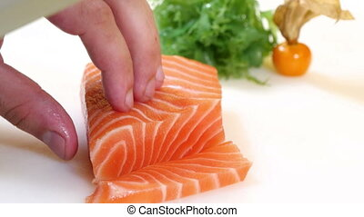 Sushi Chef Slices a Salmon Steak - A sushiman slicing a...