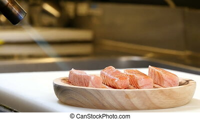 Chef Cooking Salmon with Torch - A sushiman cooking pieces...