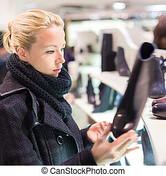 Beautiful woman shopping in shoe store. - Woman shopping...