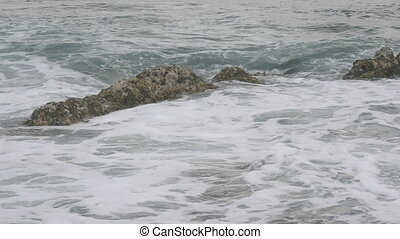 Waves spashing on submerged rock - Waves wash over an...
