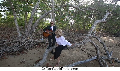 girl stands up of branch guitarist stops to play at trees -...
