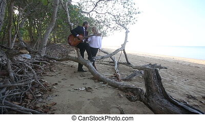 guitarist and blonde girl talk near tropical trees branches