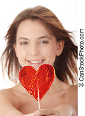 Sensual girl with heart shaped lolipop, isolated on white
