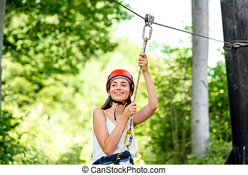 Woman riding on a zip line - Young and pretty woman in red...
