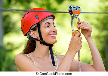 Woman riding on a zip line - Young and smiling woman in red...