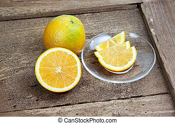 Orange sliced in half and thinly sliced on old table wood