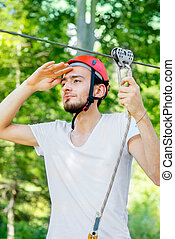 Man riding on a zip line - Young man in red helmet preparing...