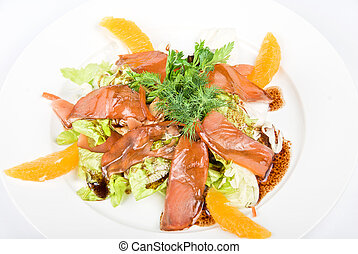 Tasty salad dish close up with fish and oranges on a white...