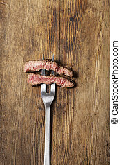 slices of a steak on a meat fork