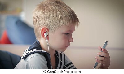 Little boy with a happy face listening to music