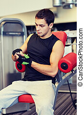 young man with smartphone in gym - sport, bodybuilding,...
