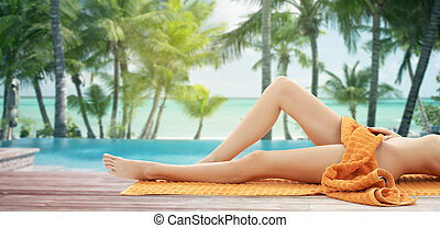 close up of woman legs with orange towel on beach - people,...