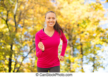 smiling woman running outdoors at autumn - fitness, sport,...