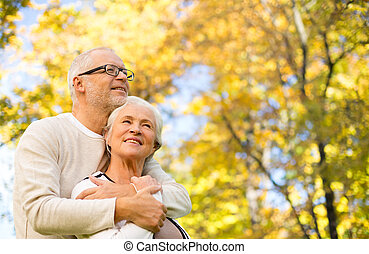 happy senior couple in autumn park - family, age, season and...