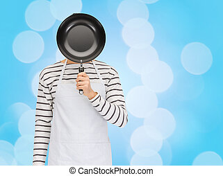 man or cook in apron hiding face behind frying pan - people,...