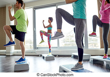 group of people raising legs on step platforms - fitness,...