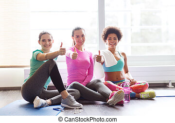 happy women with water showing thumbs up in gym - fitness,...