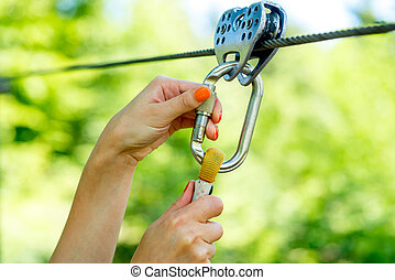 Carabine on a zip line - Female hands holding carabine on a...
