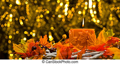 Orange candle in autumn Christmas setting in front of a...