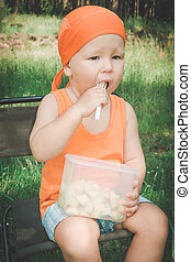 Baby eating - Cute baby eating fruits outdoor