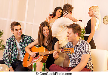 Girl Playing Guitar At House Party