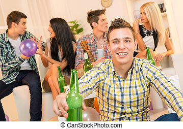 House Party - A young guy at a home party, with a smile on...