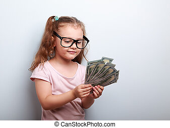 Happy kid girl in glasses looking and counting the money