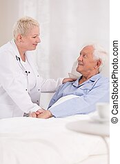Nurse taking care about patient - Photo of mature nurse...