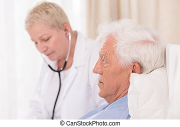 Doctor with stethoscope examining patient